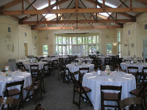 Inside the Celebration Center Building, with round tables, white table cloths, and chairs setup for an event.